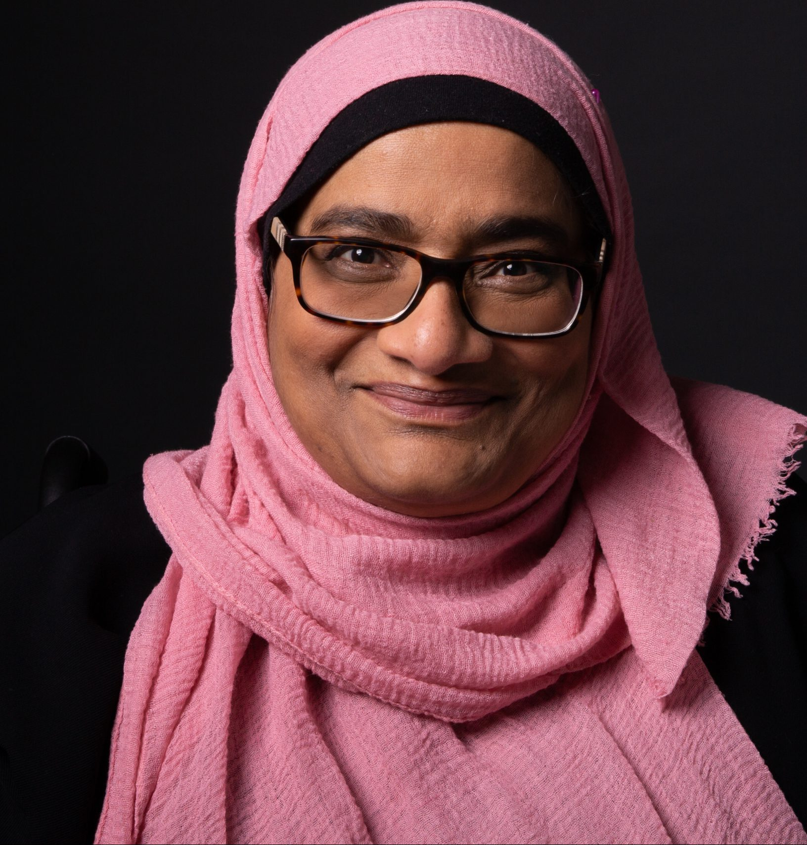 Rafia: Smiling wearing pink hijab and glasses with black background, picture is up to just below the shoulders.