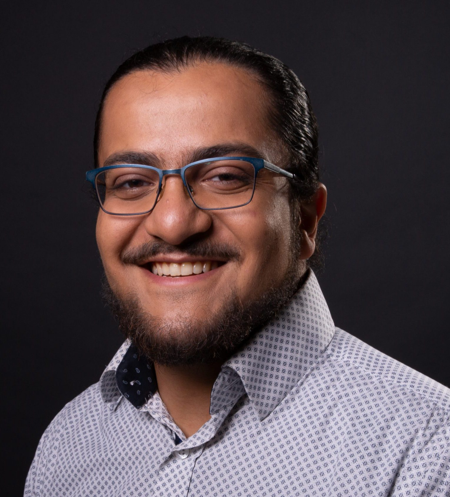 Omar: Smiling looking at camera with a black background, with blue printed dress shirt and blue framed glasses, picture is up to just below the shoulders.