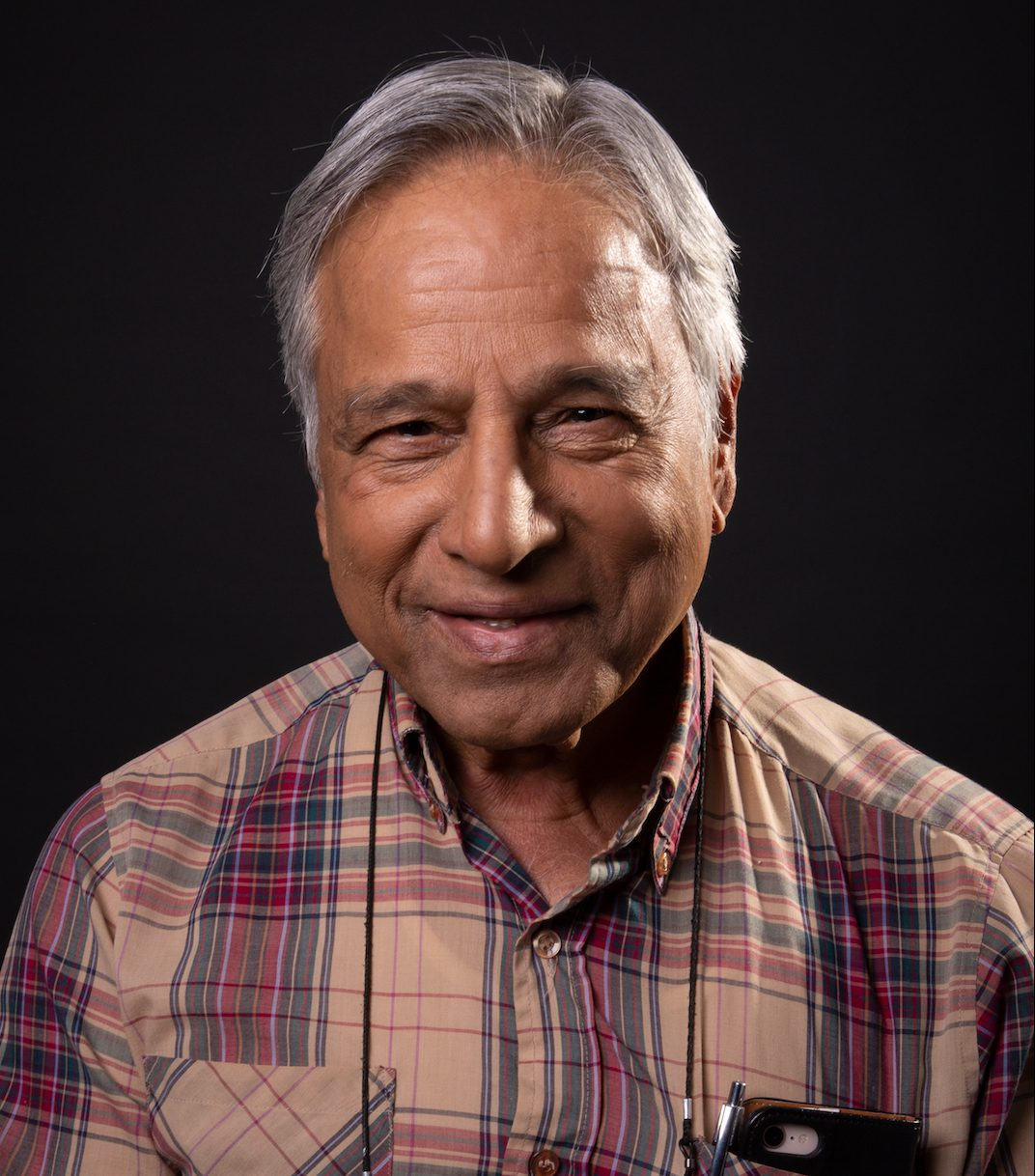 Nazar: Smiling at camera, with black background. Wearing a patterned dress shirt that is brown, maroon and dark blue, picture is up to just below the shoulders.