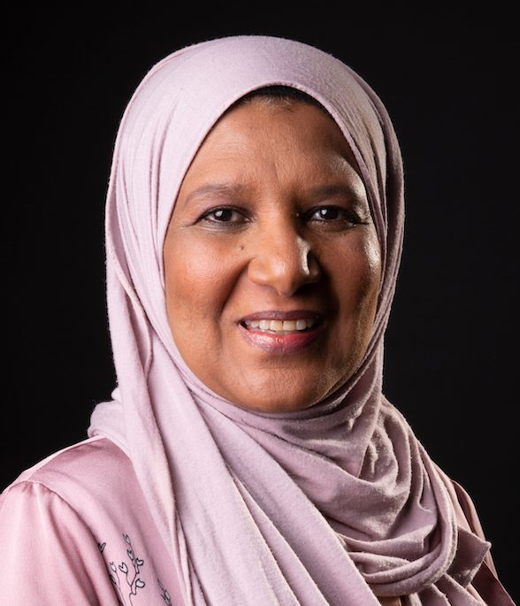 Suda: Smiling looking at camera, with black background. Wearing a light pink hijab and light pink top as well, picture is up to just below the shoulders.