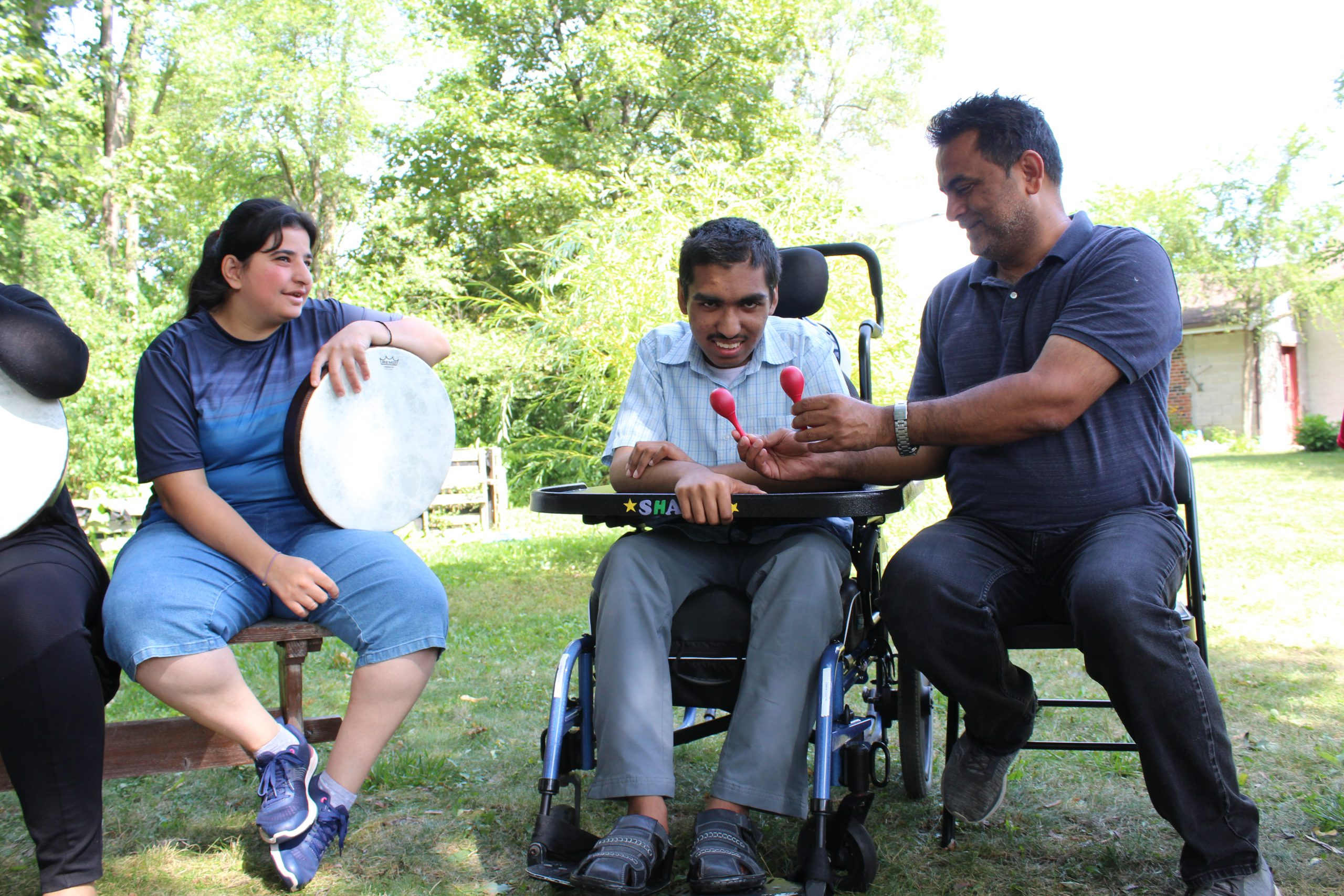 One male staff sitting outdoors on the right side offering shakers to the participant. Male participant being offered shakers is in manual wheelchair in the middle with female participant holding a duff sitting beside him on a bench.