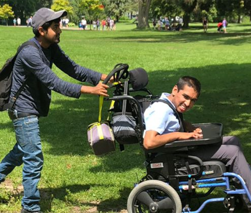Male participant wearing backpack and cap is pushing another male participant in a wheelchair in a park with green grass.