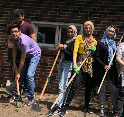 left to right, two male volunteers and three female volunteers holding shovels and cleaning yard at muneeba center.