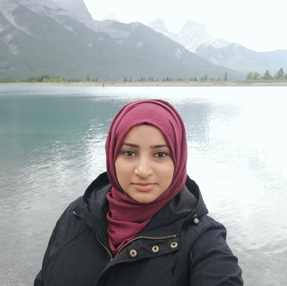 Faiza Hashmi: Smiling with lake and mountain view background wearing black jacket and red hijab, picture is up to just below the shoulders.