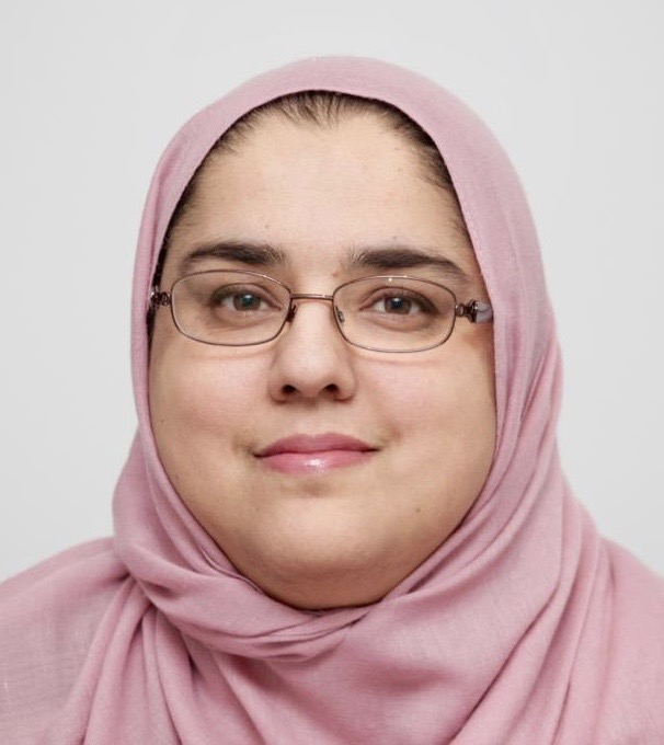 Zainab Khan: Smiling with a light grey background, wearing light pink hijab and glasses, picture is up to just below the shoulders.
