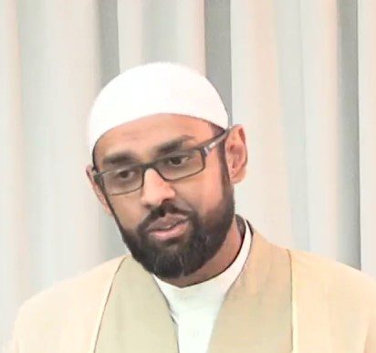 Sh. Jaffer: Light coloured background that are curtains. Wearing white hat, and light tan colored top with white under. Black framed glasses and short beard. Picture is up to just below the shoulders.