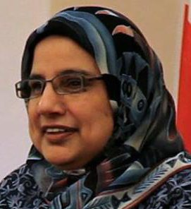 Sr. Shahina: Light background, wearing dark blue hijab, with glasses. Picture is up to the shoulders.