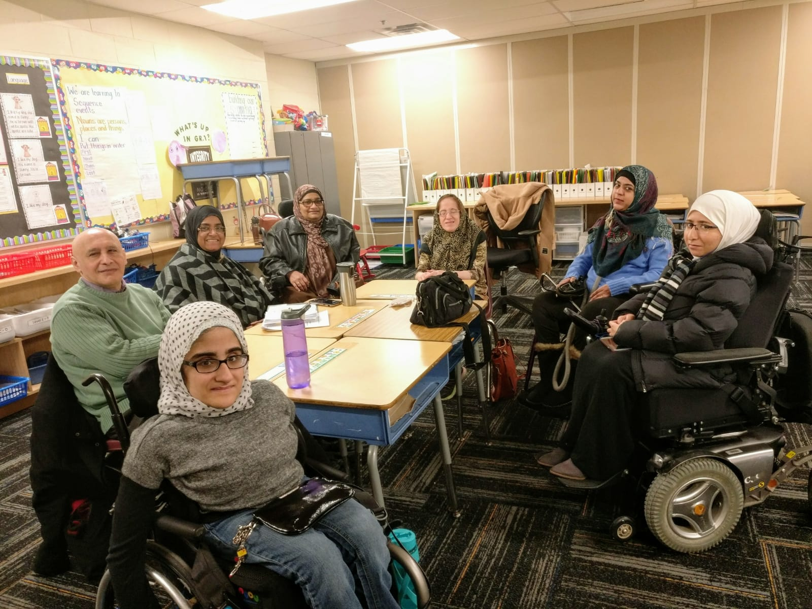 Six females and one male sitting in wheelchairs around tables.
