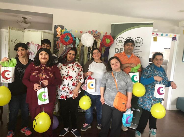 8 participants standing in the Muneeba center infront of DEEN banner holding their Ramadan crescent moon art work along with yellow ballons. Six females and two males.