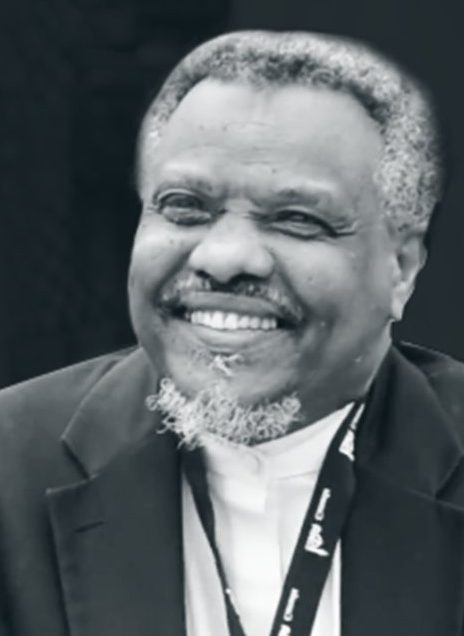 Sheikh Abdalla Idris Ali: Smiling, black and white picture. Has some facial hair, picture is up to just below the shoulders.