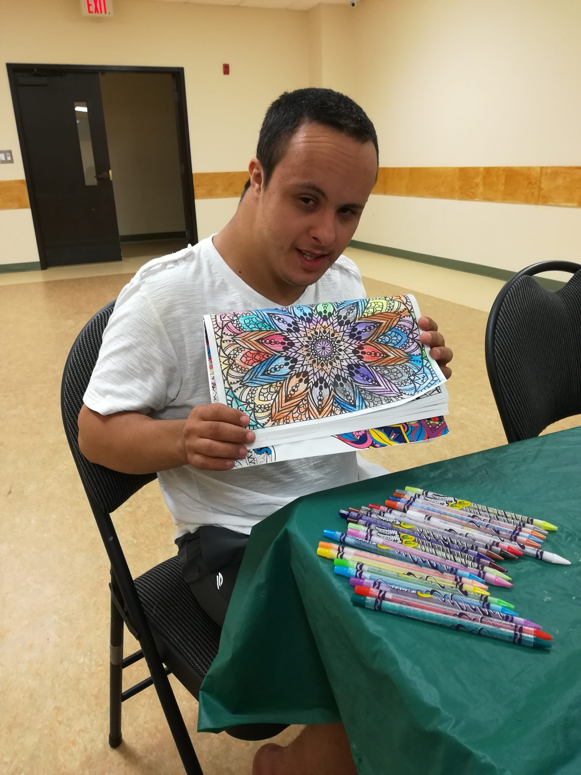 Male participant holding a coloring book showing his work of the mandala he colored.